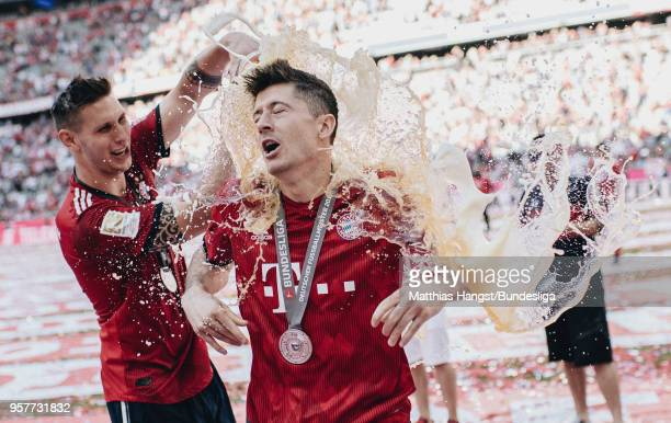 Robert Lewandowksi of FC Bayern Muenchen gets a beer shower by Niklas Suele of FC Bayern Muenchen after the Bundesliga match between FC Bayern...