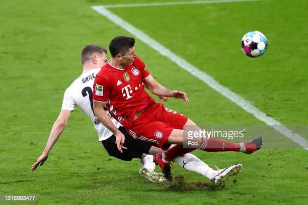 Robert Lewandowski of FC Bayern Muenchen is challenged by Matthias Ginter of Borussia Moenchengladbach during the Bundesliga match between FC Bayern...