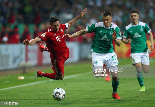 Robert Lewandowski of FC Bayern Muenchen is challenged by Maximilian Eggestein of Bremen during the DFB Cup semi final match between Werder Bremen...