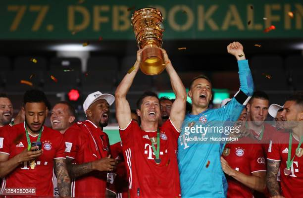 Robert Lewandowski of FC Bayern Muenchen lifts the trophy in celebration with his team mates after the DFB Cup final match between Bayer 04...