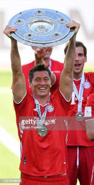 Robert Lewandowski of FC Bayern Muenchen lifts the trophy to celebrate the championship following the Bundesliga match between VfL Wolfsburg and FC...