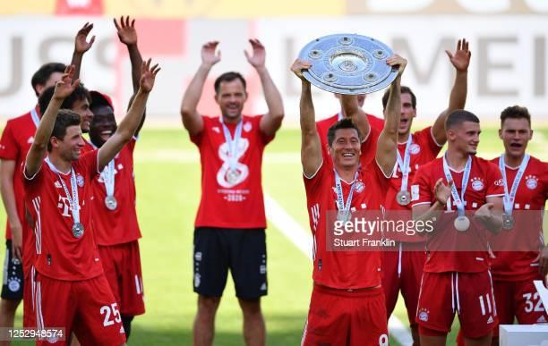 Robert Lewandowski of FC Bayern Muenchen lifts the trophy to celebrate the championship following the Bundesliga match between VfL Wolfsburg and FC...