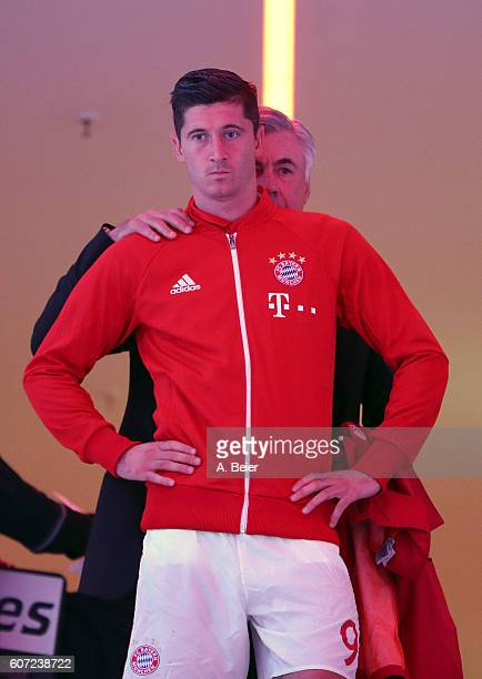 Robert Lewandowski of FC Bayern Muenchen listens to his team coach Carlo Ancelotti in the players' tunnel ahead of the Bundesliga match between...