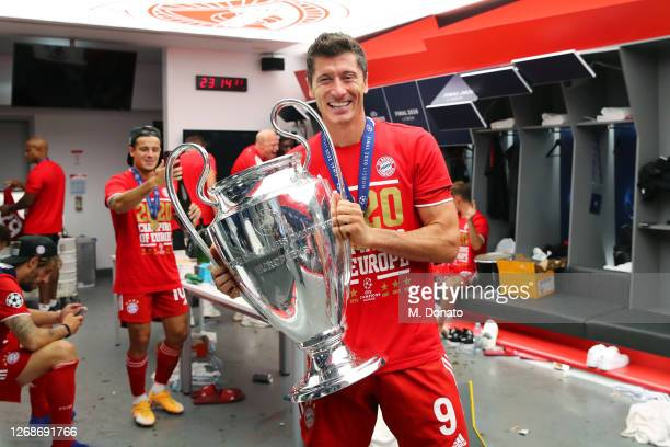 Robert Lewandowski of FC Bayern Muenchen poses with the trophy in the dressing room following his team's victory in the UEFA Champions League Final...