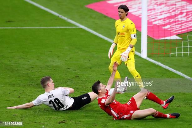 Robert Lewandowski of FC Bayern Muenchen reacts after a challenged by Matthias Ginter of Borussia Moenchengladbach during the Bundesliga match...