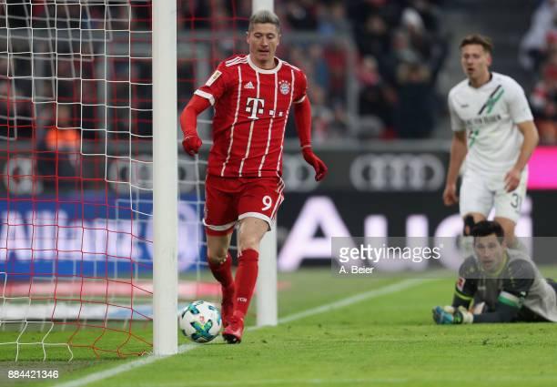 Robert Lewandowski of FC Bayern Muenchen scores his first goal against goalkeeper Philipp Tschauner of Hannover 96 during the Bundesliga match...