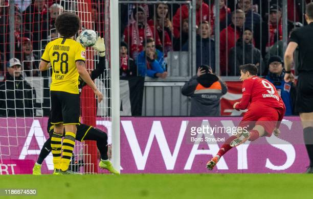 Robert Lewandowski of FC Bayern Muenchen scores his team's first goal with a header past goalkeeper Roman Buerki of Borussia Dortmund during the...