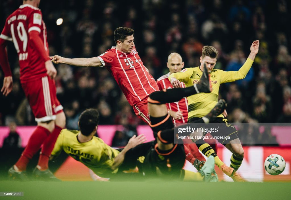 Robert Lewandowksi of FC Bayern Muenchen scores his team's sixth goal past Sokratis Papastathopoulos of Dortmund and Goalkeeper Roman Buerki of Dortmund during the Bundesliga match between FC Bayern Muenchen and Borussia Dortmund at Allianz Arena on April 1, 2018 in Munich, Germany.