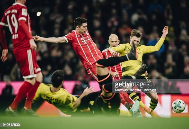 Robert Lewandowski of FC Bayern Muenchen scores his team's sixth goal past Sokratis Papastathopoulos of Dortmund and Goalkeeper Roman Buerki of...