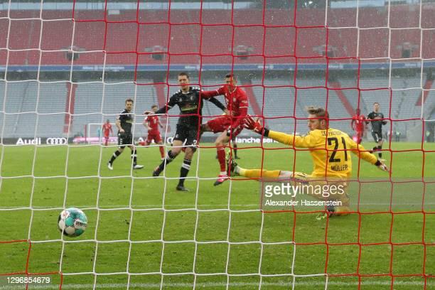 Robert Lewandowski of FC Bayern Muenchen scores their sides first goal past Florian Müller of SC Freiburg during the Bundesliga match between FC...