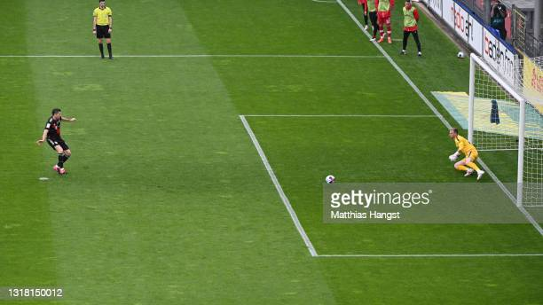 Robert Lewandowski of FC Bayern Muenchen scores their side's first goal past Mark Flekken of Sport-Club Freiburg from the penalty spot scoring his...