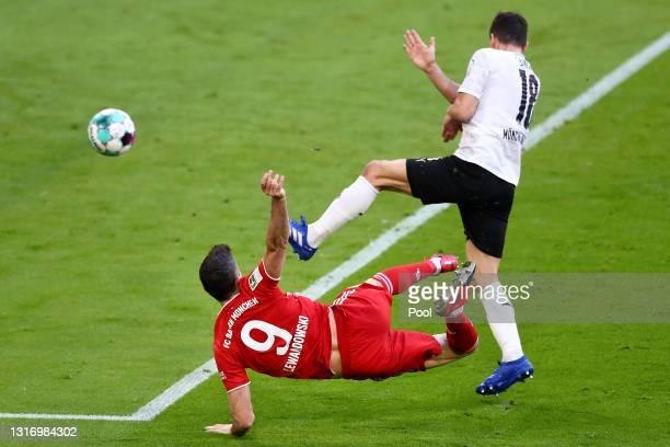 Robert Lewandowski of FC Bayern Muenchen scores their side's third goal whilst under pressure from Stefan Lainer of Borussia Moenchengladbach during...