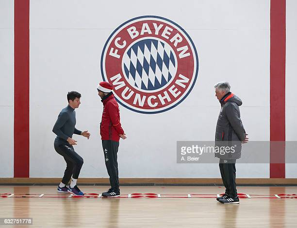Robert Lewandowski of FC Bayern Muenchen warms up next to team coach Carlo Ancelotti and assistent coach Davide Ancelotti during a training session...