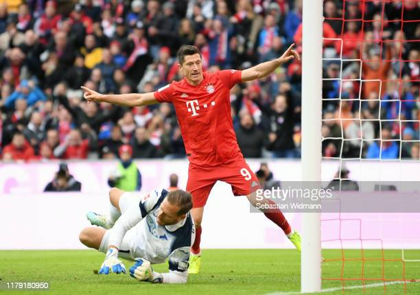 Robert Lewandowski of FC Bayern Munich celebrates after scoring his team's first goal as Oliver Baumann of TSG 1899 Hoffenheim reacts during the...