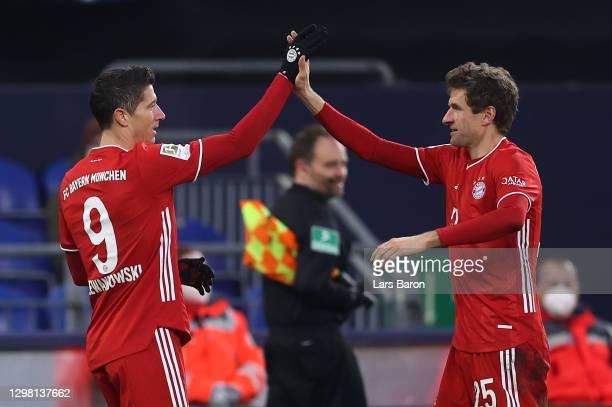 Robert Lewandowski of FC Bayern Munich celebrates with team mate Thomas Muller after scoring their side's second goal during the Bundesliga match...