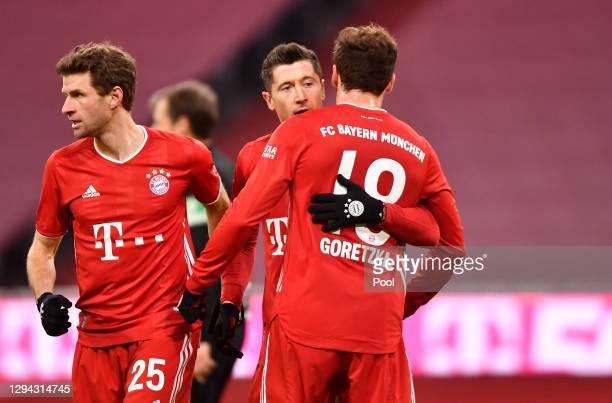 Robert Lewandowski of FC Bayern Munich celebrates with team mates Leon Goretzka and Thomas Muller after scoring their sides fourth goal during the...