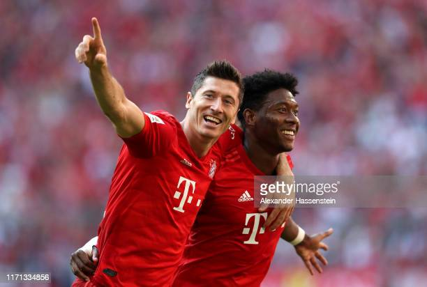 Robert Lewandowski of FC Bayern Munich celebrates with teammate David Alaba after scoring his team's fifth goal during the Bundesliga match between...