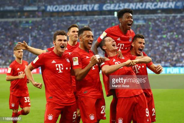Robert Lewandowski of FC Bayern Munich celebrates with teammates after scoring his team's second goal during the Bundesliga match between FC Schalke...