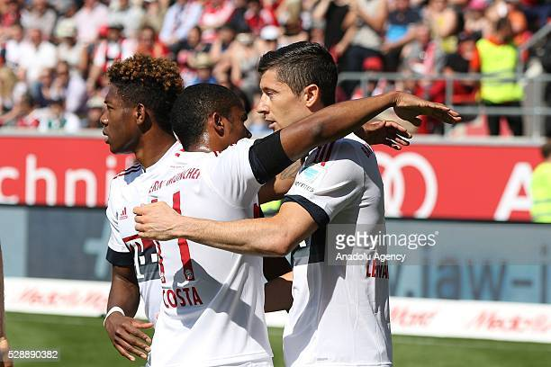Robert Lewandowski of FC Bayern Munich celebrates with teammates Douglas Costa and David Alaba after scoring a goal during the Bundesliga football...