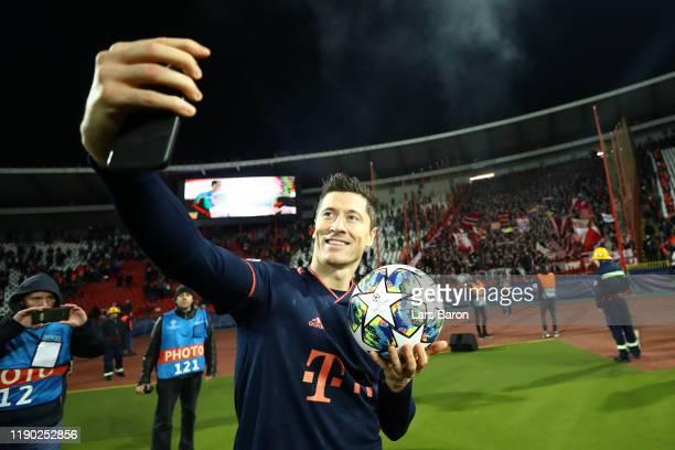 Robert Lewandowski of FC Bayern Munich celebrates with the match ball following his four goals during the UEFA Champions League group B match between...