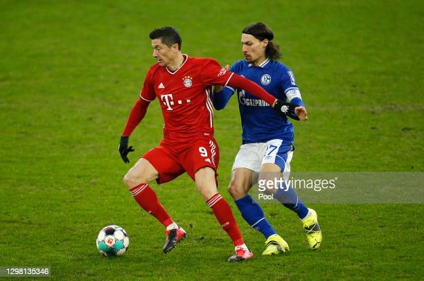 Robert Lewandowski of FC Bayern Munich is challenged by Benjamin Stambouli of FC Schalke 04 during the Bundesliga match between FC Schalke 04 and FC...