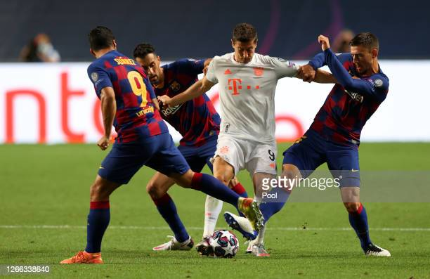 Robert Lewandowski of FC Bayern Munich is challenged by Luis Suarez, Sergio Busquets, and Clement Lenglet of FC Barcelona during the UEFA Champions...