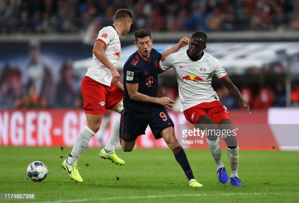 Robert Lewandowski of FC Bayern Munich is stopped by Ibrahima Konate and Willi Thomas Orban of RB Leipzig during the Bundesliga match between RB...