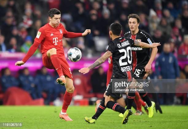 Robert Lewandowski of FC Bayern Munich passes the ball under pressure from Julian Baumgartlinger and Charles Aranguiz of Bayer 04 Leverkusen during...