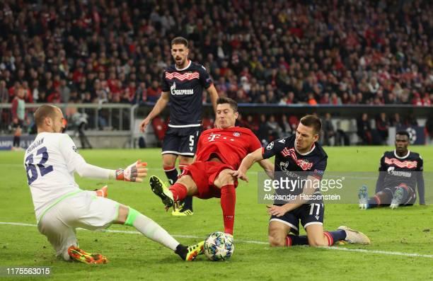 Robert Lewandowski of FC Bayern Munich scores his sides first goal past Milan Borjan of Crvena Zvezda under pressure from Marko Gobelijic of Crvena...