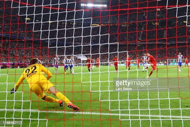 Robert Lewandowski of FC Bayern Munich scores his team's second goal from the penalty spot past Rune Jarstein of Hertha BSC during the Bundesliga...