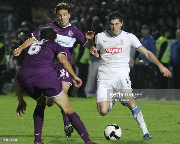 Robert Lewandowski of Lech Poznan fights for ball with Joachim Standfest and Jacek Bak of Austria Wien during their UEFA Cup final round...
