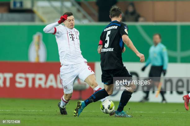 Robert Lewandowski of Muenchen and Christian Strohdiek of Paderborn battle for the ball during the DFB Cup match between SC Paderborn and Bayern...