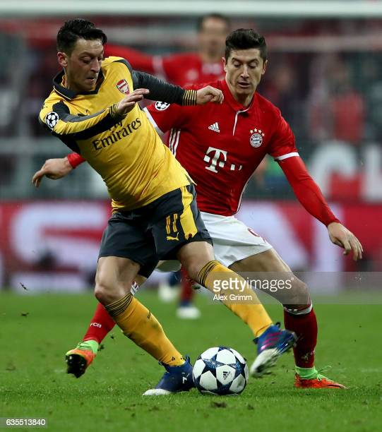 Robert Lewandowski of Muenchen and Mesut Oezil of Arsenal battle for the ball during the UEFA Champions League Round of 16 first leg match between FC...