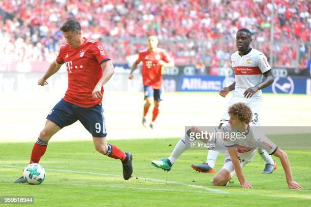 Robert Lewandowski of Muenchen Benjamin Pavard of Stuttgart and Orel Mangala of Stuttgart battle for the ball during the Bundesliga match between FC...