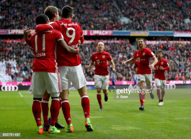 Robert Lewandowski of Muenchen celebrate with team mate Thomas Mueller and Douglas Costa after he scores the opening goal during the Bundesliga match...