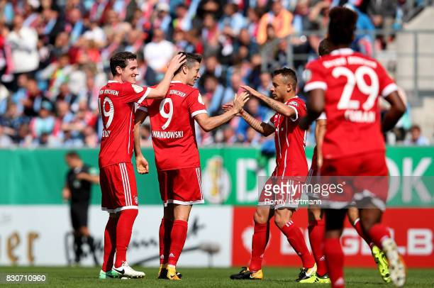 Robert Lewandowski of Muenchen celebrates after scoring his team's opening goal with Sebastian Rudy and Rafinha of Muenchen during the DFB Cup first...
