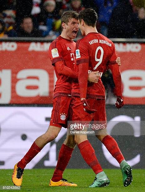 Robert Lewandowski of Muenchen celebrates his team's first goal with team mate Thomas Mueller during the Bundesliga match between FC Ausgburg and FC...