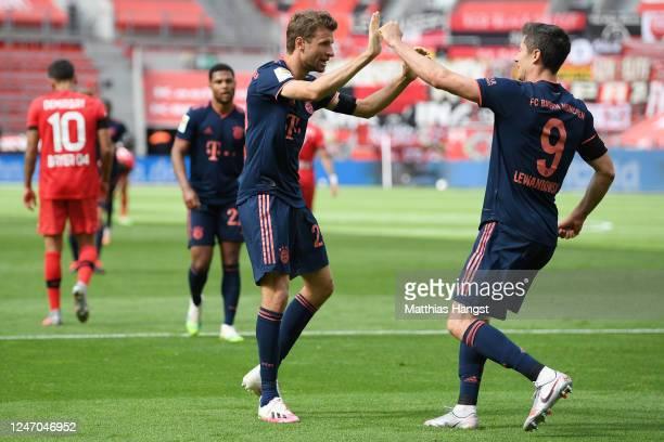Robert Lewandowski of Muenchen celebrates his team's fourth goal with teammate Thomas Mueller during the Bundesliga match between Bayer 04 Leverkusen...