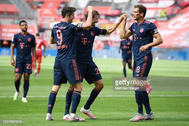Robert Lewandowski of Muenchen celebrates his team's fourth goal with teammates Thomas Mueller and Leon Goretzka during the Bundesliga match between...