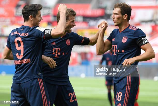 Robert Lewandowski of Muenchen celebrates his team's fourth goal with teammates Thomas Mueller and Leon Goretzka during the Bundesliga match between...