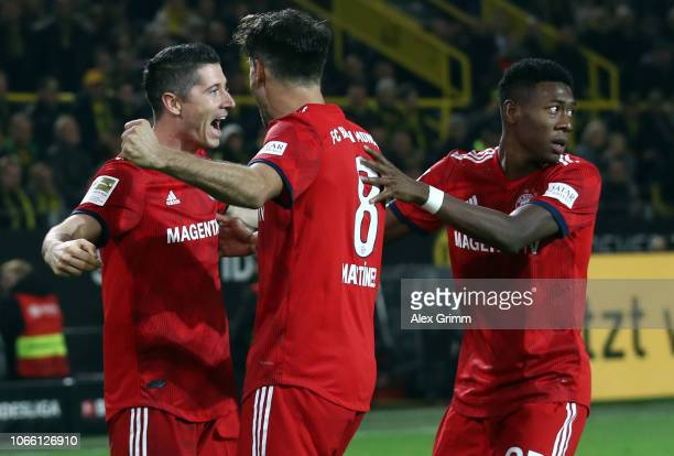 Robert Lewandowski of Muenchen celebrates his team's second goal with team mates Javi Martinez and David Alaba during the Bundesliga match between...