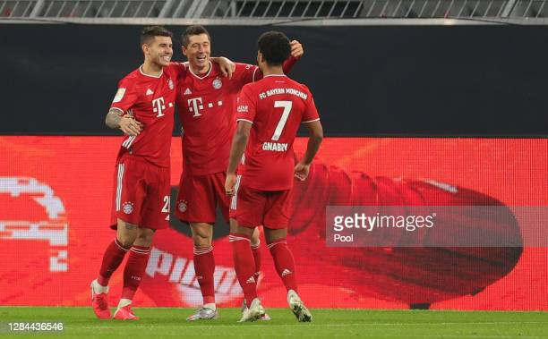 Robert Lewandowski of Muenchen celebrates his team's second goal with teammates Lucas Hernandez and m during the Bundesliga match between Borussia...
