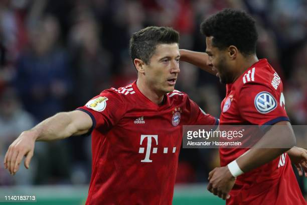 Robert Lewandowski of Muenchen celebrates his team's third goal with team mate Serge Gnabry during the DFB Cup quarterfinal match between Bayern...