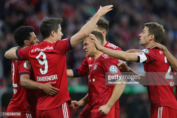 Robert Lewandowski of Muenchen celebrates his team's third goal with team mates during the DFB Cup quarterfinal match between Bayern Muenchen and 1...