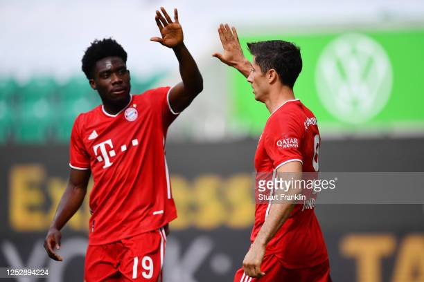 Robert Lewandowski of Muenchen celebrates his team's third goal with teammates Alphonso Davies during the Bundesliga match between VfL Wolfsburg and...