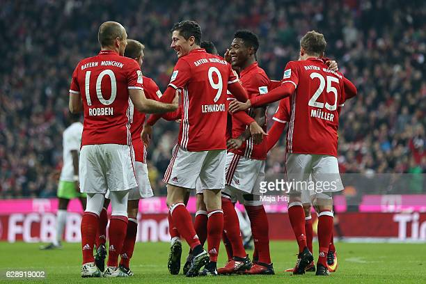 Robert Lewandowski of Muenchen celebrates his team's third goal with team mates during the Bundesliga match between Bayern Muenchen and VfL Wolfsburg...