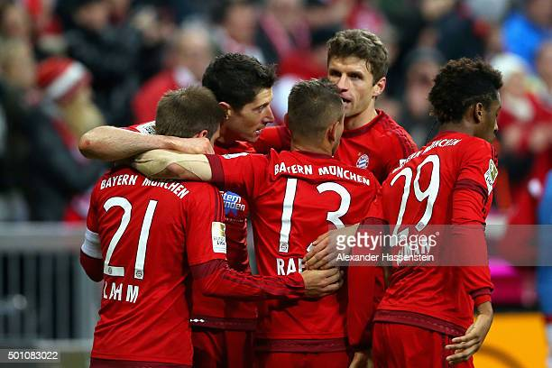 Robert Lewandowski of Muenchen celebrates scoring the opening goal with his team mates during the Bundesliga match between FC Bayern Muenchen and FC...
