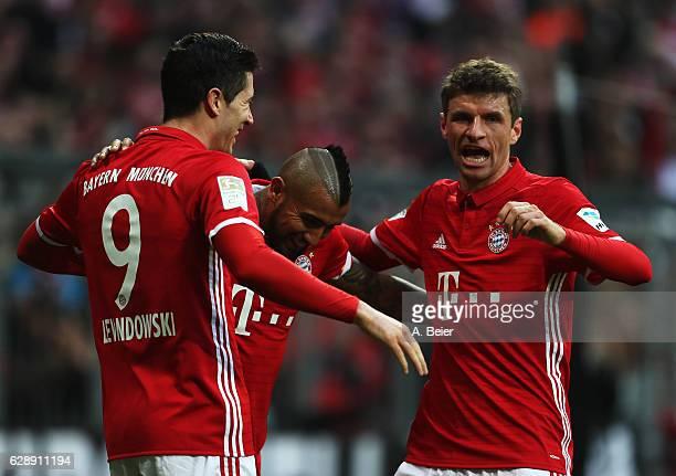 Robert Lewandowski of Muenchen celebrates scoring the second goal with Arturo Vidal and Thomas Mueller during the Bundesliga match between Bayern...