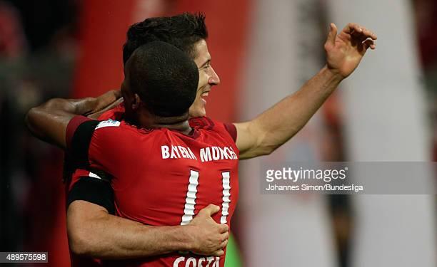 Robert Lewandowski of Muenchen celebrates with team mate Douglas Costa after scoring his team's 3rd goal during the Bundesliga match between FC...