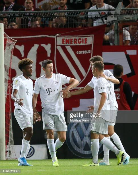 Robert Lewandowski of Muenchen celebrates with teammates after scoring his team's first goal during the DFB Cup first round match between FC Energie...